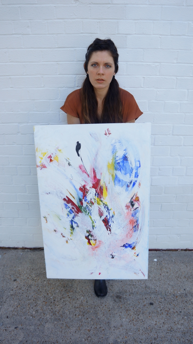 Artist Rachael Harbert holds painting Pinata in portrait view while standing in front of a white block wall