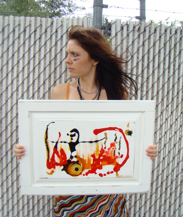 "Artist Rachael Harbert holds painting ""Pyromaniac"" in front of white barbed fence"