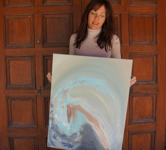 "Artist Rachael Harbert holds painting ""Rising"" in front of large, oak doors"