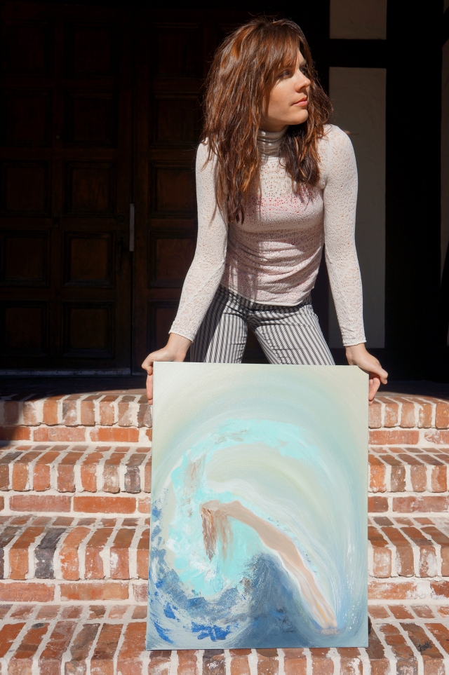 "Artist Rachael Harbert holds painting ""Rising"" on shallow brick steps"