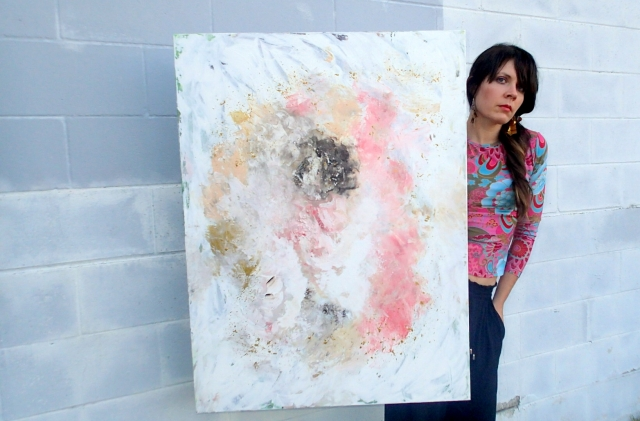 Artist Rachael Harbert holds painting Salt and Sand in front of a multi-gray wall