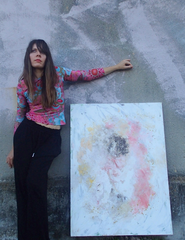 Artist Rachael Harbert holds painting Salt and Sand in front of a green and pink wall