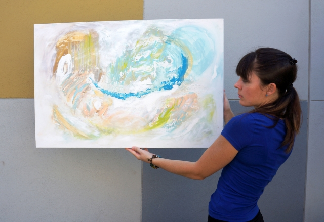Artist Rachael Harbert holds painting Sea Foam in front of a yellow, gray and white color block wall