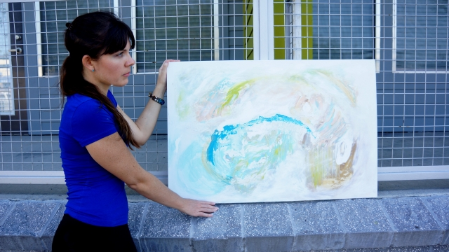 Artist Rachael Harbert holds painting Sea Foam in front of a gray and green patio with metal fencing