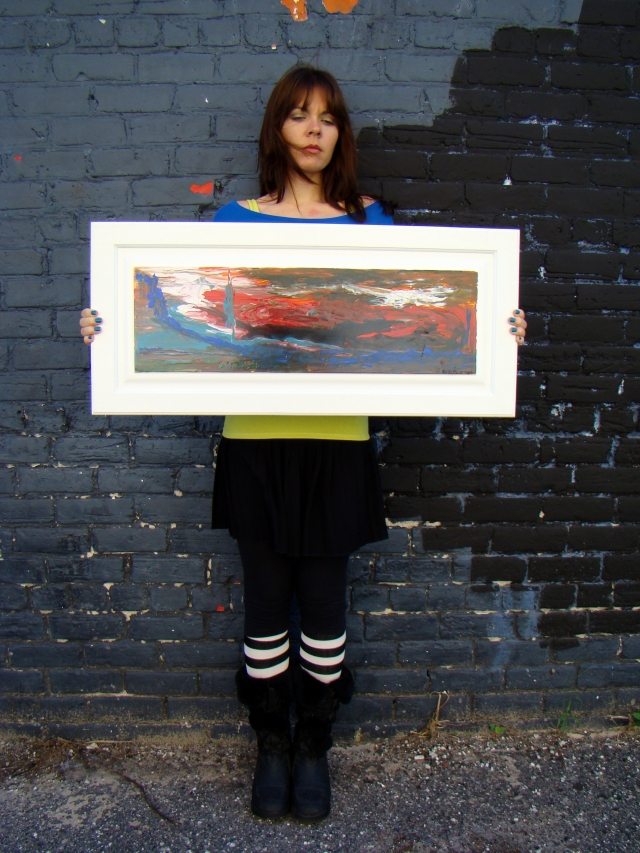 "Artist Rachael Harbert holding abstract painting ""Sky on Fire"" in front of a two-toned black brick building"