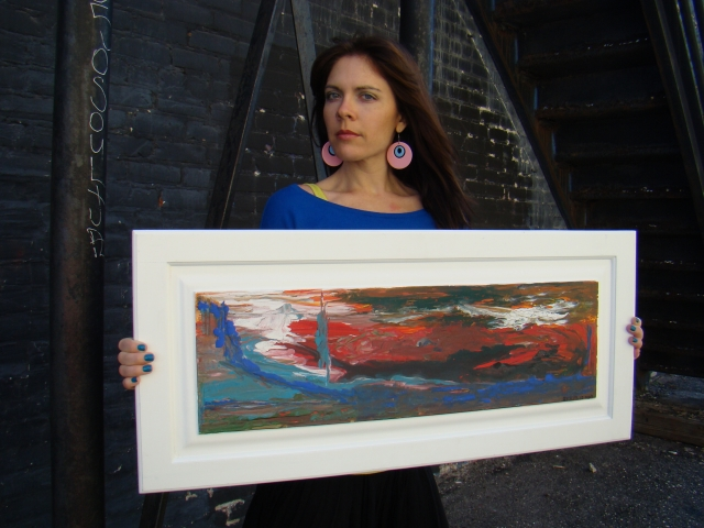 "Artist Rachael Harbert holding abstract painting ""Sky on Fire"" in front of a black brick building"