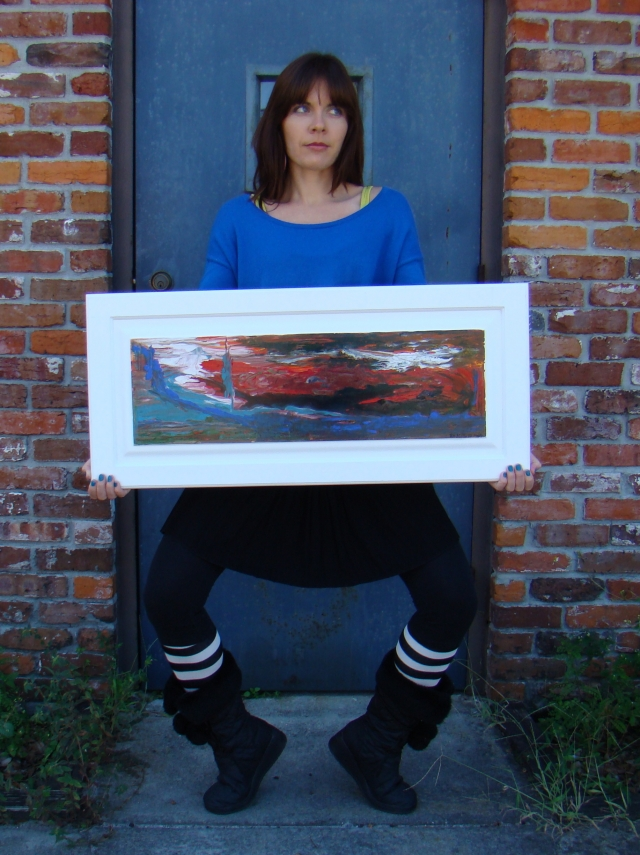 """Artist Rachael Harbert holding abstract painting """"Sky on Fire"""" in front of a blue door and brick wall"""