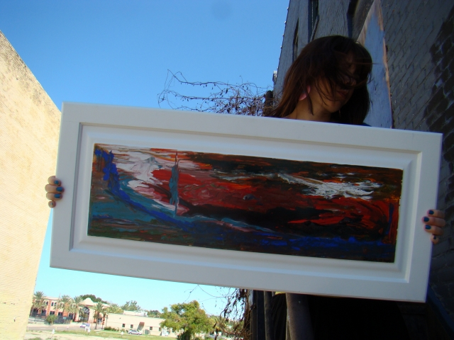 """Artist Rachael Harbert holding abstract painting """"Sky on Fire"""" as she stands on a staircase"""