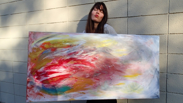 Artist Rachael Harbert holds painting Smoke and Flames as she purses her lips
