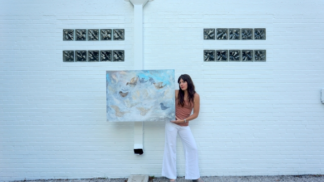 Artist Rachael Harbert holds abstract painting Sparrows in front of a white brick wall decorated by block glass windows