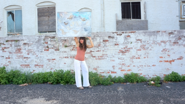 Artist Rachael Harbert holds abstract painting Sparrows in front of a white chipped brick wall accented by broken windows