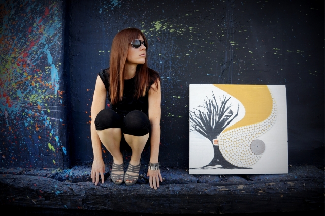 """Artist Rachael Harbert crouched next to abstract painting """"Spun Gold"""" against a wall of splattered paint"""