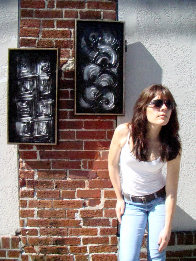 Artist Rachael Harbert stands next to paintings Squares and Swirls as they hang on a brick square column