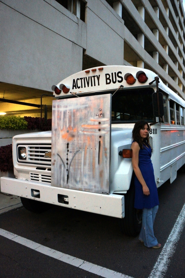 "Artist Rachael Harbert stands next to a bus where abstract painting ""Sterling"" sits"