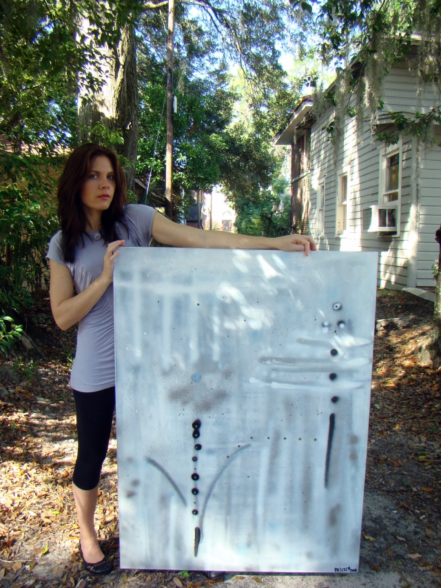 "Artist Rachael Harbert holds abstract painting ""Sterling"" as she stands in a street"