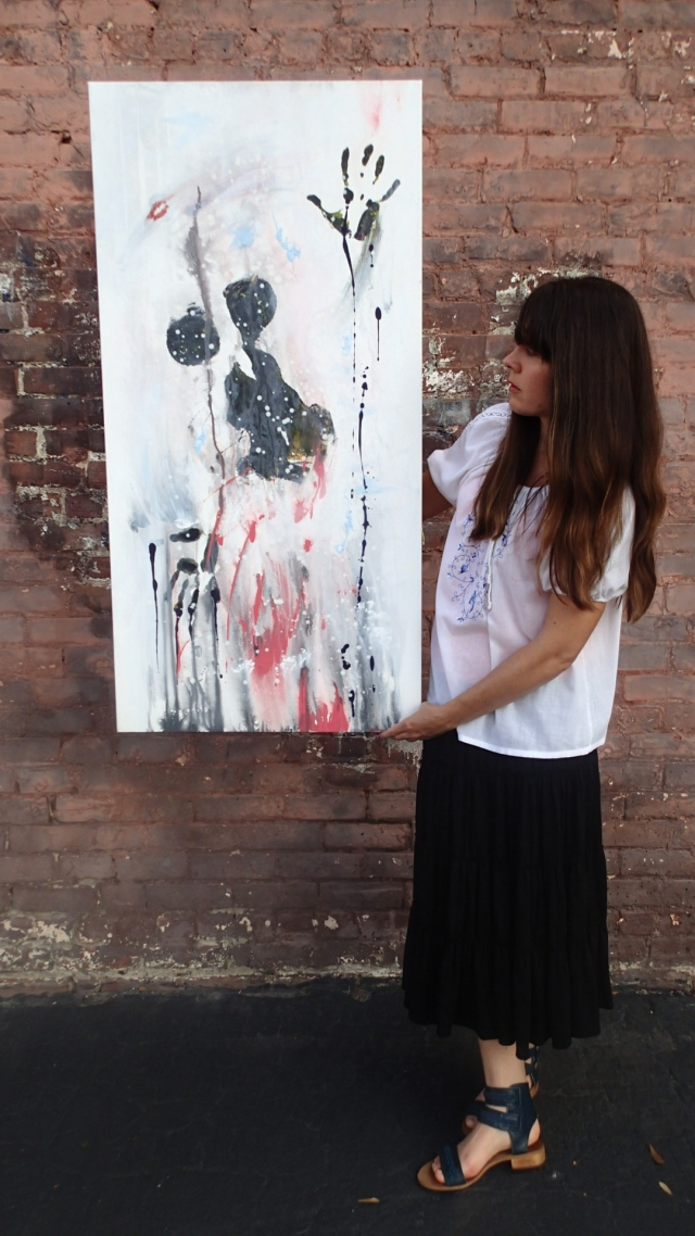 "Artist Rachael Harbert holds painting ""Still Shot"" in front of a brick wall"