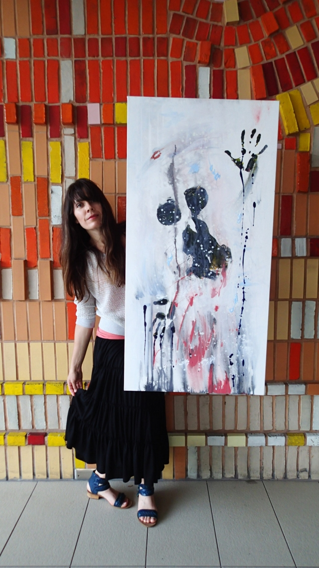 "Artist Rachael Harbert holds painting ""Still Shot"" in front of a red, orange and yellow mosaic wall"