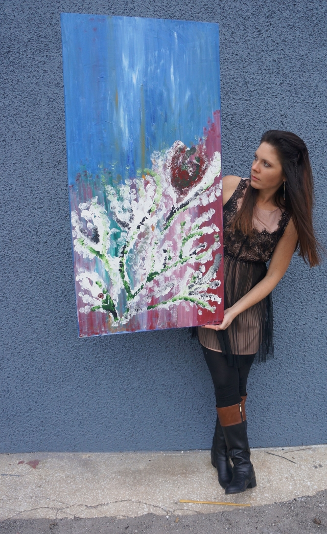 "Artist Rachael Harbert holds painting ""Thirsty"" in front of a blue gray cement wall"