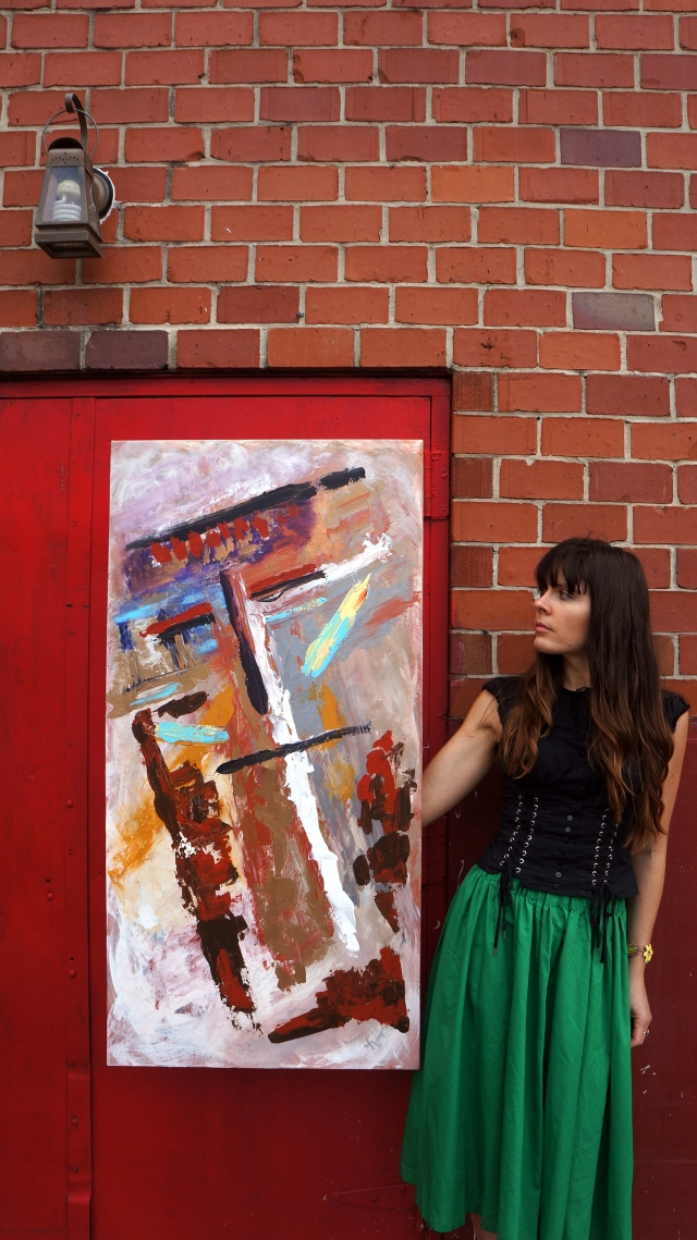 Artist Rachael Harbert holds painting Totem Pole in front of a brick building with a red door and antique lamp