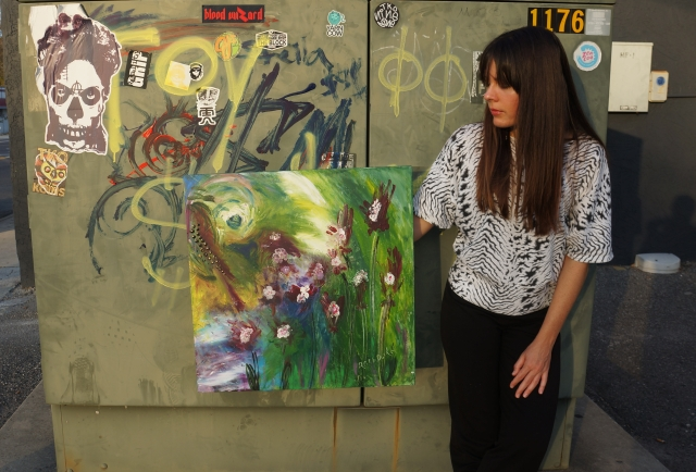 Artist Rachael Harbert holds painting Wild Jungle in front of a green electrical box covered in graffiti