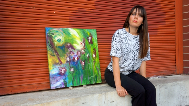 Artist Rachael Harbert sits next to painting Wild Jungle as it leans against a large red metal door