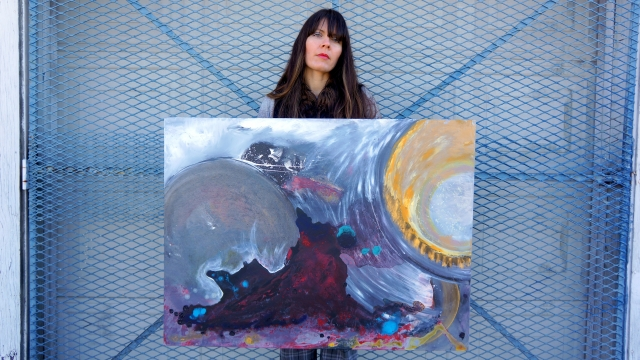 Artist Rachael Harbert holds painting Yearning for Light in front of an industrial chain door