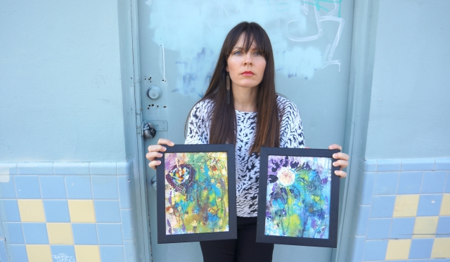 Artist Rachael Harbert holds paintings Ink Flowers 1 and Ink Flowers 2 in front of a blue graffiti door