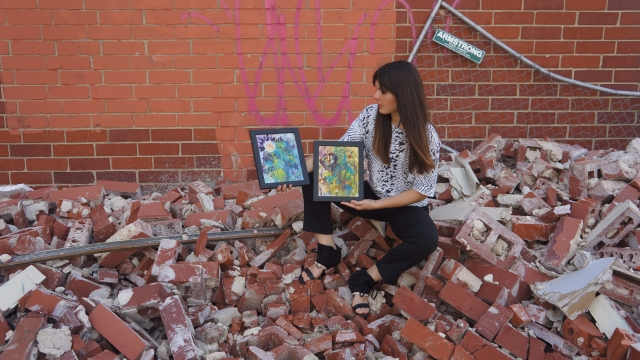 Artist Rachael Harbert holds paintings Ink Flowers 1 and Ink Flowers 2 as she sits on a large pile of rubble