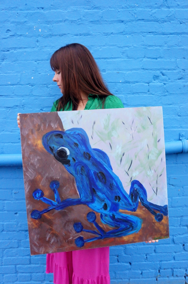 "Artist Rachael Harbert holding painting ""Cobalt Frog"" in front of a blue wall 1"