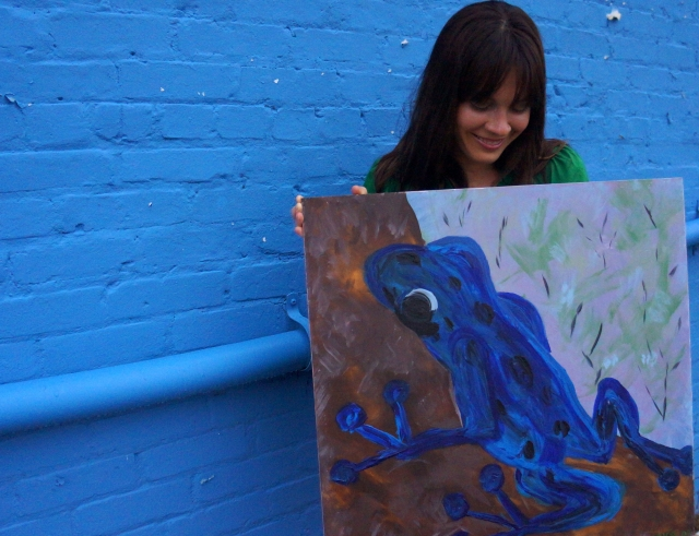 "Artist Rachael Harbert holding painting ""Cobalt Frog"" in front of a blue wall 2"