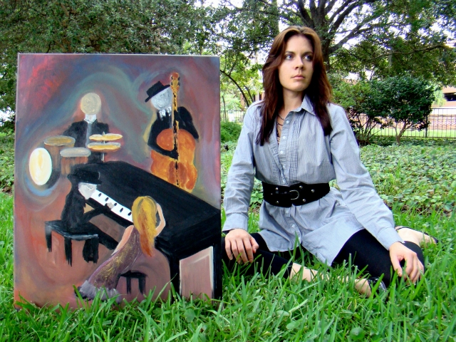 "Artist Rachael Harbert sitting next to painting ""Ensemble"" as it sits on grass in a park"