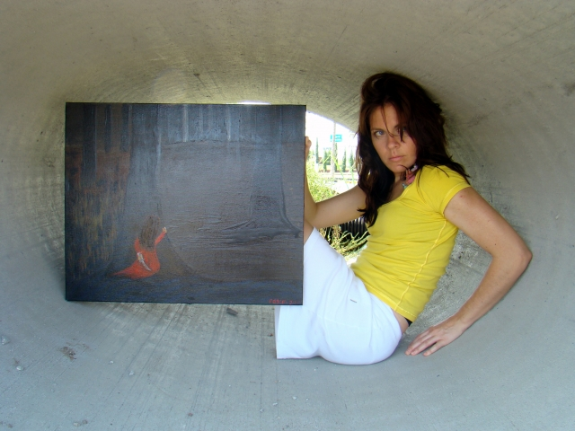 """Artist Rachael Harberts holds painting """"The Escape"""" as she is confined within a small cement cylinder"""