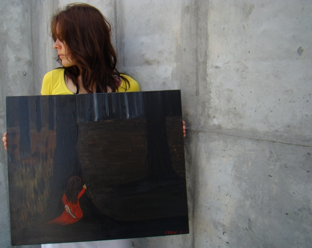 """Artist Rachael Harberts holds painting """"The Escape"""" as she stands in a large cement cylinder"""