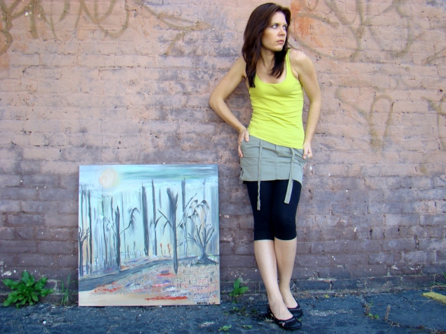 "Artist Rachael Harbert stands next to painting ""Knightley Trail"" as it leans against a graffiti and brick wall"