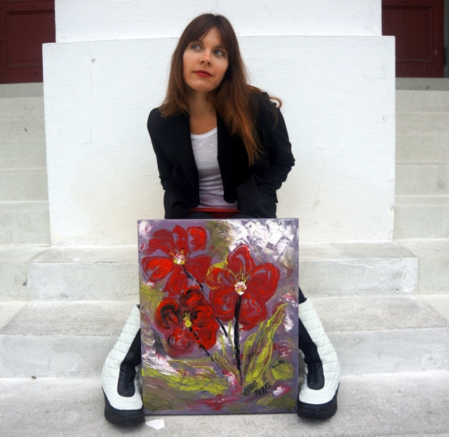 "Artist Rachael Harbert sits on white cement steps as painting ""Red Impatients"" leans against her"