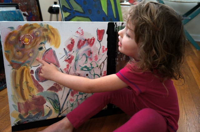 "Little girl holds painting ""Rosaly"" and points to the painting in awe of the painting"