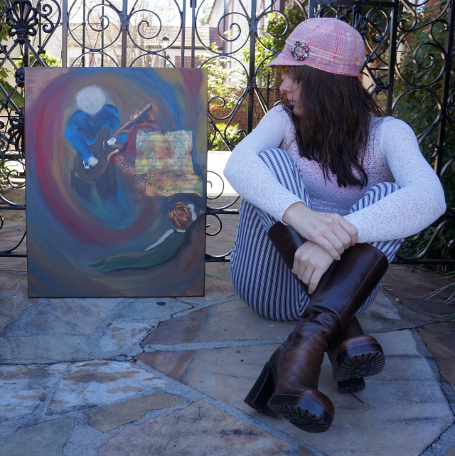 "Artist Rachael Harbert sits next to and looks at painting ""Since I Met You Baby"" as it leans against an iron gate"