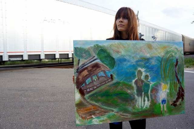 """Artist Rachael Harbert holds painting """"Smith Mountain Lake"""" as a train whizzes by"""