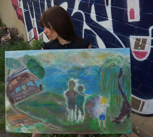 """Artist Rachael Harbert holds painting """"Smith Mountain Lake"""" in front of a blue graffiti wall"""