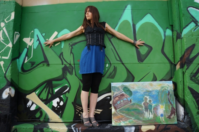 """Artist Rachael Harbert holds painting """"Smith Mountain Lake"""" in front of a green graffiti wall"""