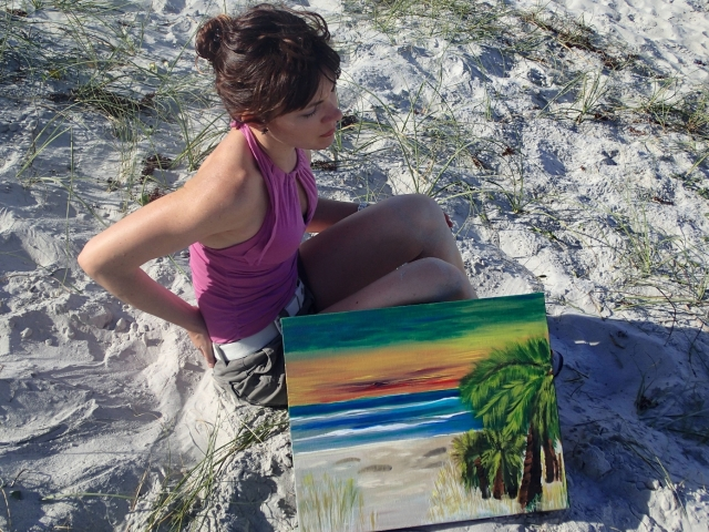 "Artist Rachael Harbert sits on the beach with painting ""Sunset on the Shore"""