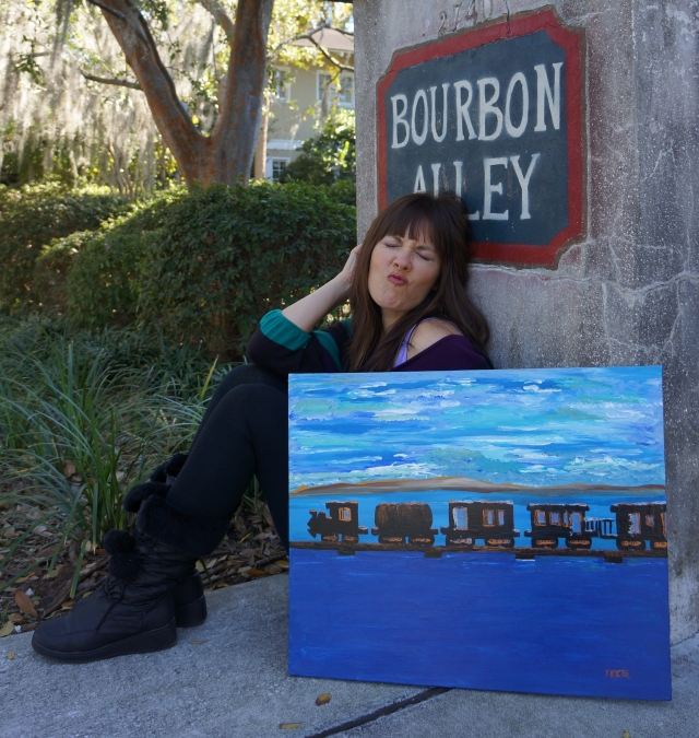 "Artist Rachael Harbert sits behind painting ""Train Over Water"" as it leans against a wall with Bourbon Alley written on it"