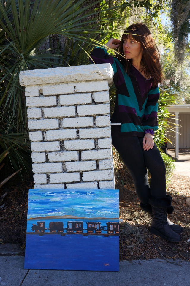 "Artist Rachael Harbert stands next to painting ""Train Over Water"" as it leans against a white brick column"