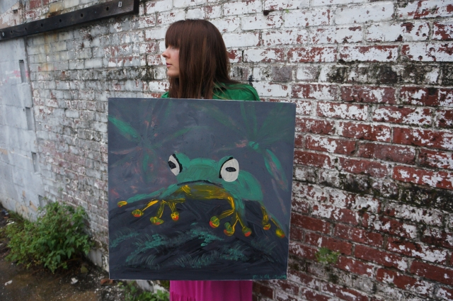 """Artist Rachael Harbert holds painting """"Tree Frog"""" in front of a red and white brick wall"""