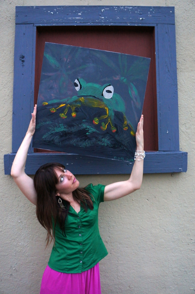 """Artist Rachael Harbert holds painting """"Tree Frog"""" in a pseudo window on a wall"""