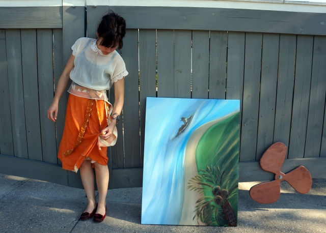 """Artist Rachael Harbert standing next to a gray fence with a red motor boat blade and the painting """"Balcony View"""""""
