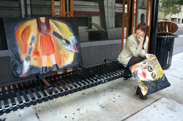 """Artist Rachael Harbert sitting at a bus stop looking at painting """"Blade Assassin"""" which sits on a bench"""