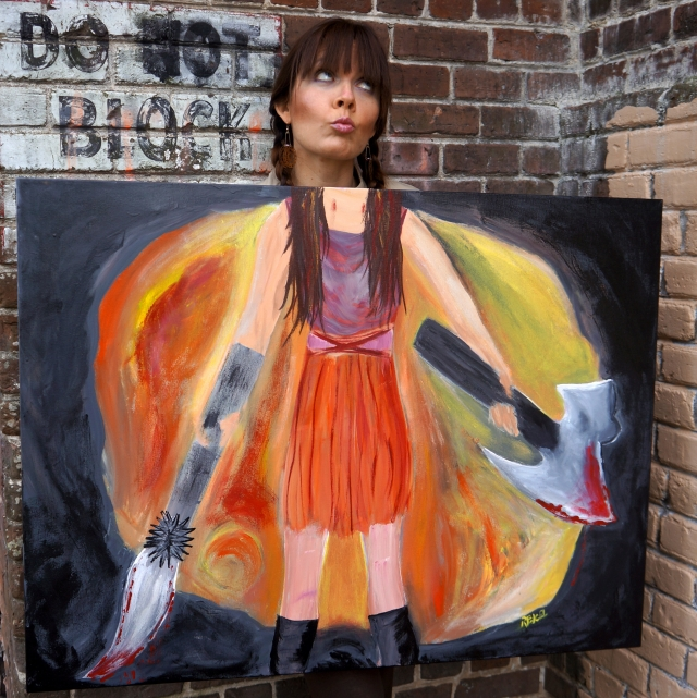 "Artist Rachael Harbert holding painting ""Blade Assassin"" against a brick wall with a Do Not Block sign - 1"