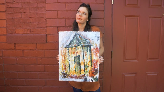 Artist Rachael Harbert holds painting Cottage in front of a rust red wall