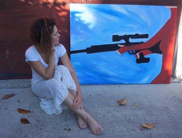 """Artist Rachael Harbert sits on cement looking back at painting """"Rifle Assassin"""" as it leans against a red garage door"""